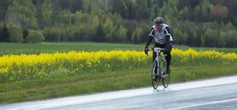 Um participante em uma raça menor da bicicleta para ambos os profissionais e Fotografia de Stock