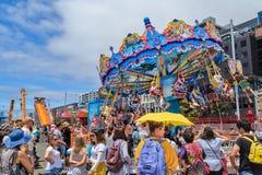Um passeio do carrossel do balanço em uma feira, olhada por uma grande multidão imagens de stock