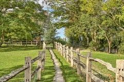 Um passeio rural que passa entre duas cercas de madeira fotos de stock