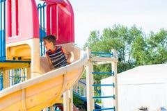 Um patim alegre do menino em uma montanha russa do ` s das crianças no parque fotografia de stock royalty free