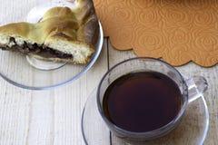 Um pedaço de bolo enchido com as cerejas e as nozes do doce da maçã e um copo do chá estão na tabela fotos de stock royalty free