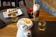 Um pedaço de bolo, um milk shake em um vidro, um bule, copos do chá e cutelaria em uma tabela em um café foto de stock