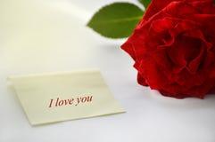 Um pedaço de papel ao lado dele é uma rosa vermelha Lugar para o texto e os cumprimentos Cartão romântico Fundo delicado, bonito fotografia de stock