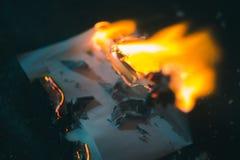 Um pedaço de papel carbonizado em um ferro escuro do fundo imagem de stock royalty free