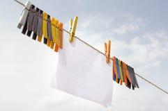 Um pedaço de papel que pendura no cabo com clothespins Imagens de Stock Royalty Free
