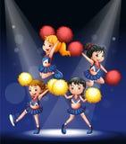 Um pelotão cheering com os pompoms vermelhos e amarelos Imagens de Stock Royalty Free