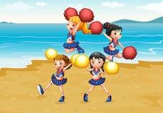 Um pelotão cheering que executa na praia Imagens de Stock