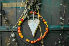 Um pendente feito de um coração de madeira e de umas maçãs secadas como um símbolo do amor imagens de stock