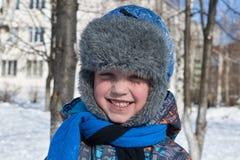 Um pequeno uma luz solar do inverno do menino um o dia aos olhares em nós e em sorrisos Fotografia de Stock