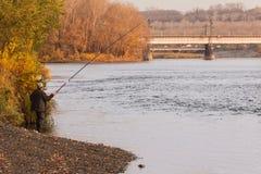 Um pescador do homem na manhã do outono joga equipamentos sobre o ri fotos de stock