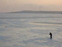 Um pescador do inverno no gelo está pescando fotografia de stock royalty free