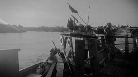 Um pescador e seu barco no porto imagens de stock royalty free