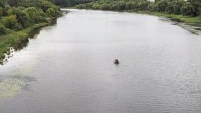 Um pescador em um barco de borracha nada no rio video estoque
