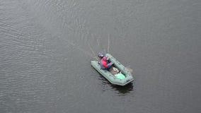 Um pescador em um barco de borracha nada no rio filme