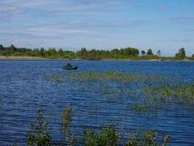 Um pescador em um barco no lago imagens de stock royalty free
