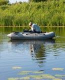 Um pescador em um barco de borracha Fotos de Stock