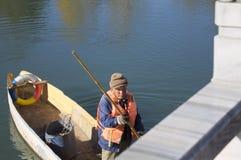 Um pescador idoso em um barco de madeira em Dragon Pool preto Fotografia de Stock Royalty Free