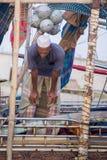 Um pescador que reza em seu barco de pesca Foto de Stock Royalty Free