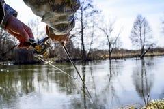 Um pescador trava um peixe Close up de giro do carretel Profundidade de campo rasa no carretel de giro foto de stock