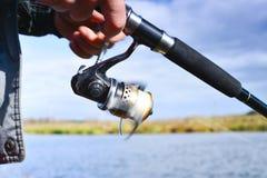 Um pescador trava um peixe Close up de giro do carretel Profundidade de campo rasa no carretel da linha de pesca imagens de stock