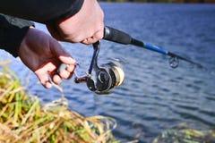 Um pescador trava um peixe Close up de giro do carretel Profundidade de campo rasa no carretel da linha de pesca fotografia de stock