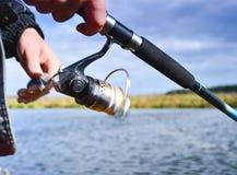 Um pescador trava um peixe Close up de giro do carretel Profundidade de campo rasa no carretel da linha de pesca imagens de stock royalty free