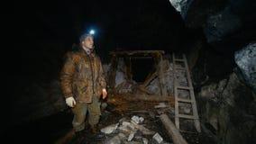 Um pesquisador com uma lanterna elétrica examina uma mina abandonada com colapsos vídeos de arquivo