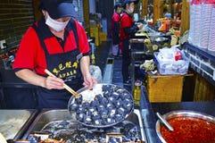 Um pessoal da tenda do alimento está preparando o Tofu fedido em Changsha China fotografia de stock