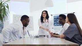 Um pessoal médico novo que aplaude ao doutor fêmea após leitura interessante na conferência no hospital Hospital video estoque
