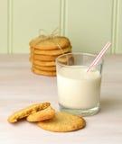 Um petisco de enchimento de cookies de manteiga caseiros do amendoim e de um vidro de refrescamento do leite com uma palha Fotos de Stock