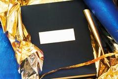 Um photobook com uma tampa de um takani azul em um envoltório do ouro do presente Imagens de Stock