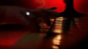 Um pianista abre uma tampa ao piano e começa a jogar um fundo amarelo vermelho filme