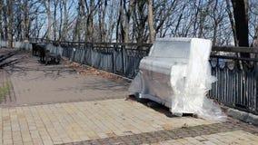 Um piano branco está no parque Ferramenta sob a película protetora video estoque
