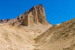 Um pico alto do deserto com penhascos completos aumenta acima de uma paisagem estéril, dourada do deserto foto de stock