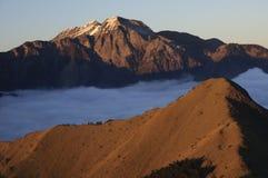 Um pico coberto de neve no por do sol Foto de Stock