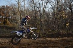 Um piloto da motocicleta aterra na roda traseira imagens de stock royalty free
