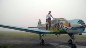 Um piloto farpado em um capacete do vintage está na asa de um avião com um tigre pintado vídeos de arquivo