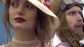 Um piloto farpado em um capacete está ao lado de uma mulher em um chapéu branco ao estilo do 60th, refocus filme