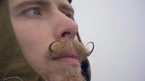Um piloto masculino luz-eyed ao estilo dos 60 suportes do ` s com um bigode torcido e dos olhares na distância filme