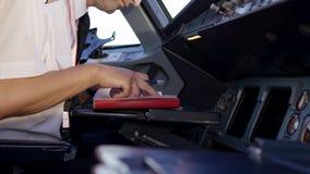 Um piloto que verifica instrumentos em uma cabina do piloto plana Ideia traseira de controles de funcionamento do piloto do jato  video estoque