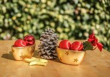 Um pinecone ao lado do Natal objeta em uma tabela de madeira Fotografia de Stock