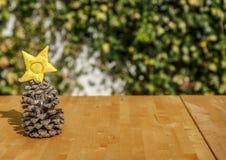 Um pinecone e uma estrela amarela em uma tabela de madeira Fotos de Stock Royalty Free