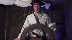 Um pirata com um chapéu armado em sua cabeça está estando antes do volante, 4k filme