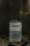 Um plástico pode com água está nas placas Fotos de Stock Royalty Free