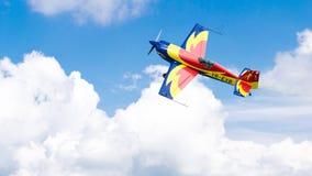 Um plano acrob?tico, voando no c?u azul com as nuvens brancas, fazendo a acrobacia foto de stock