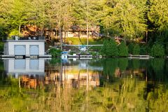 Um plano pequeno do flutuador de Cessna 182 em uma doca em uma casa de campo da beira do lago no alvorecer foto de stock royalty free