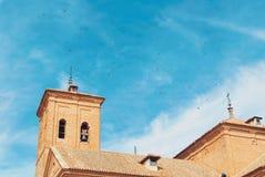 Um planty dos pombos que voam sobre o telhado de uma torre de sino de um a Imagem de Stock Royalty Free