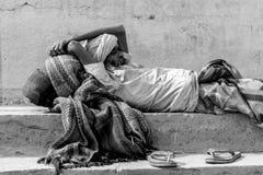 Um pobre homem que dorme no ghaat de Varanasi Ghaat de Holly Ganga fotografia de stock