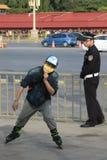 Um polícia e um homem novo em patins de rolo Pequim Fotografia de Stock Royalty Free