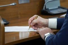 Um pol?tico ou um homem de neg?cios em um terno sentam-se em uma tabela de madeira lustrada na frente de um microfone durante uma imagem de stock royalty free